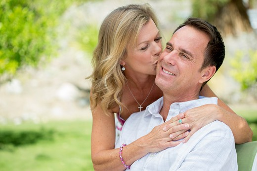 Mature woman hugging and kissing man on cheek : Stock Photo