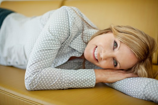Stock Photo: 4072R-133 Portrait of a mature woman resting on a couch and smiling