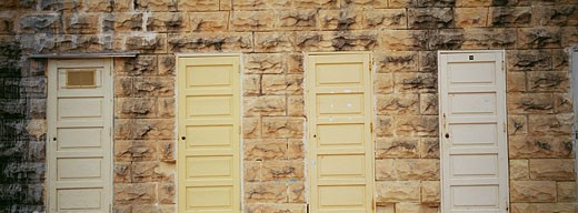 Four closed doors mounted in stone wall, St. Julian´s bay, Malta : Stock Photo