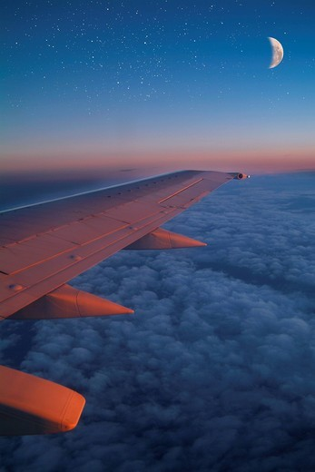 View of aeroplane wing over clouds with moon : Stock Photo