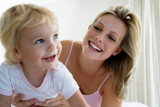 Young mother playing with baby 12_24 months in bedroom : Stock Photo