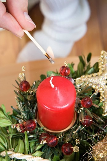 Stock Photo: 4073R-2877 Woman lighting Christmas candle