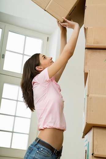 Woman stacking cardboard boxes : Stock Photo