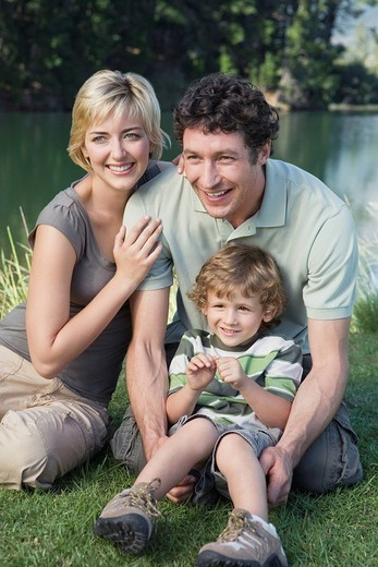 Stock Photo: 4073R-3071 Young Family with boy 4_7 sitting in front of lake, posing