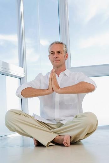 Senior man sitting, doing Yoga exercise, indoors : Stock Photo