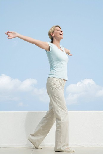 Senior woman standing on terrace with arms outstretched : Stock Photo