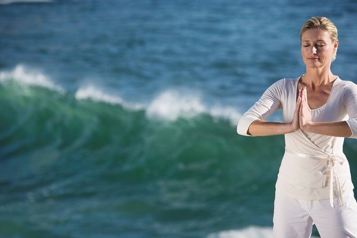 Stock Photo: 4073R-3412 Mature woman standing in prayer position, with waves breaking in background