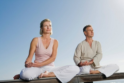 Stock Photo: 4073R-3418 Mature couple sitting cross_legged on wooden bench outdoors doing yoga