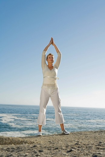 Mature woman standing on cliff, arms raised above her head doing Yoga exercises : Stock Photo