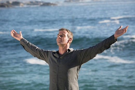 Stock Photo: 4073R-3435 Mature man with arms outstretched, smiling with ocean in background