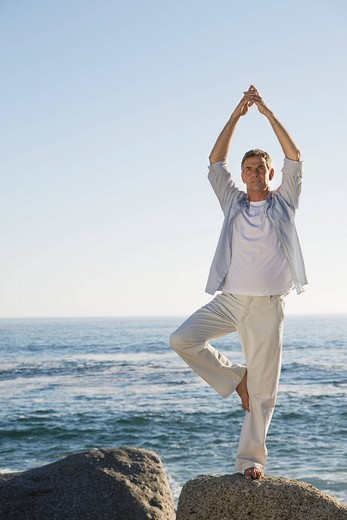 Man standing on one leg, doing yoga on top of rock with ocean in background : Stock Photo