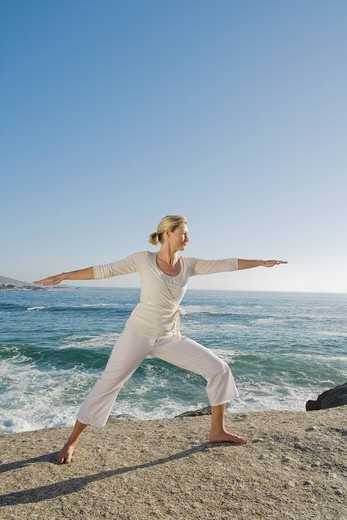 Mature woman with arms outstretched, side profile with ocean in background : Stock Photo