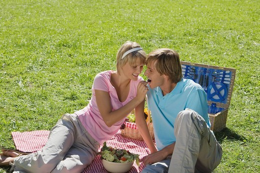 Young couple sitting on Picnic blanket woman feeding man with grapes : Stock Photo