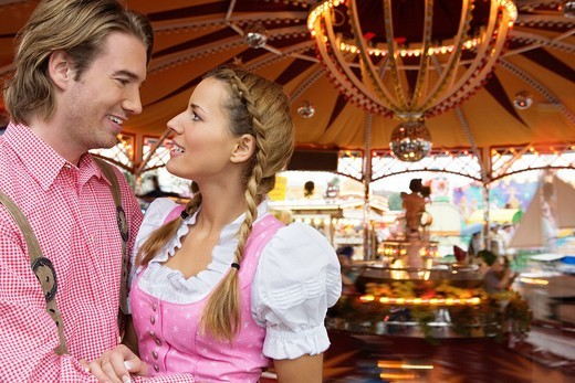 Young couple in front of fairground ride at Oktoberfest, Munich, Germany : Stock Photo