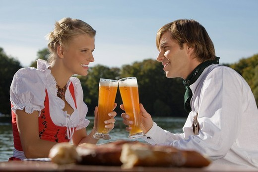 Young couple in traditional Bavarian outfit, sitting in beer garden, Munich, : Stock Photo
