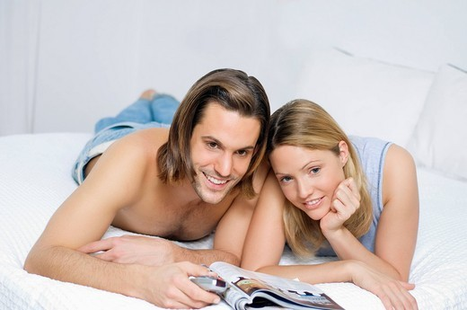 Young couple in bed, watching television : Stock Photo