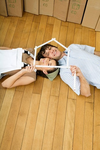 Young couple lying on wooden floor : Stock Photo