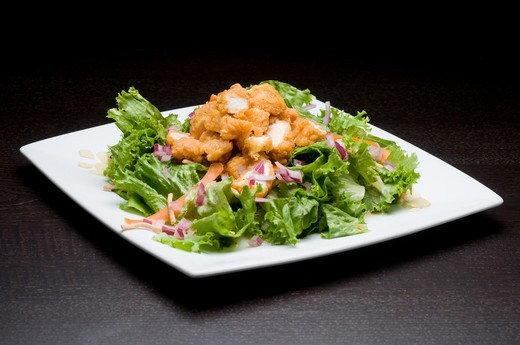 Breaded chicken with onion and carrot on lettuce leaves : Stock Photo