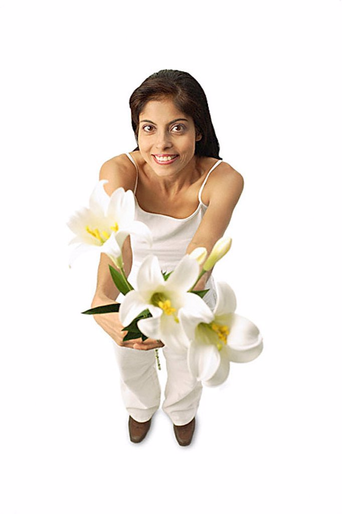 Woman standing, holding flowers, looking at camera : Stock Photo