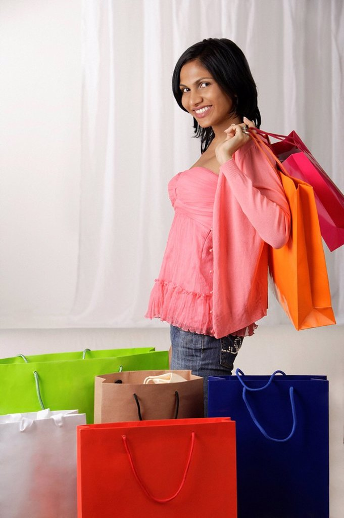 indian woman in pink blouse holding many shopping bags : Stock Photo