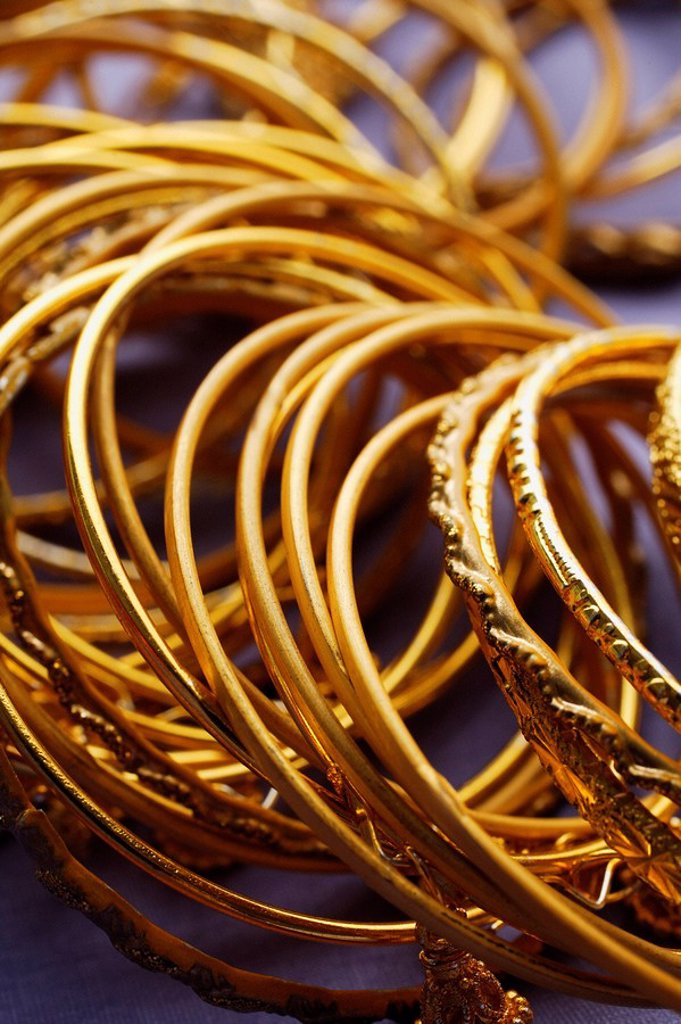 gold Indian bangles on purple sari cloth closeup : Stock Photo
