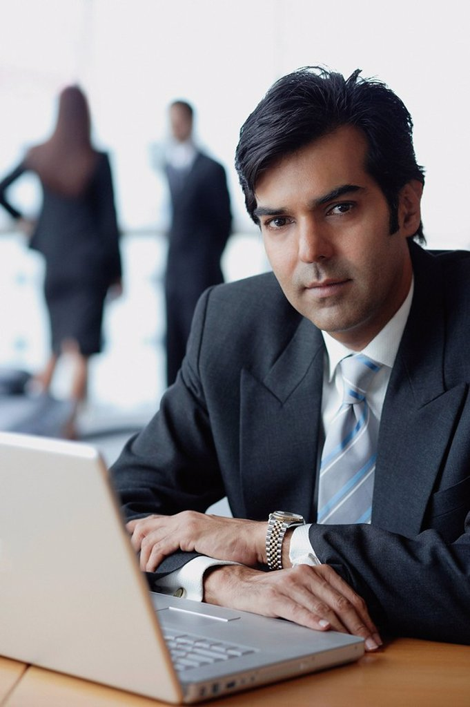 Businessman sitting in front of laptop, looking at camera : Stock Photo