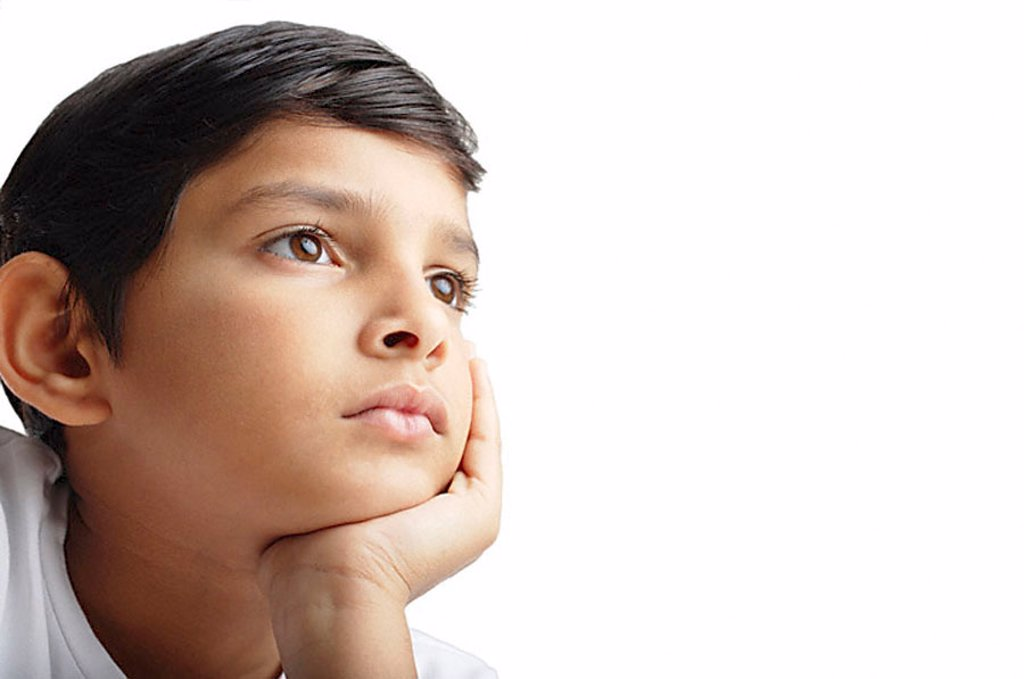 Boy with hand on chin, looking away : Stock Photo
