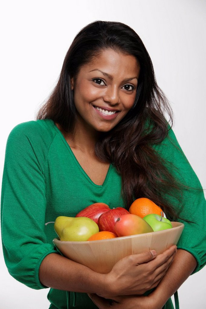Woman wearing green top holding bowl of fruit : Stock Photo