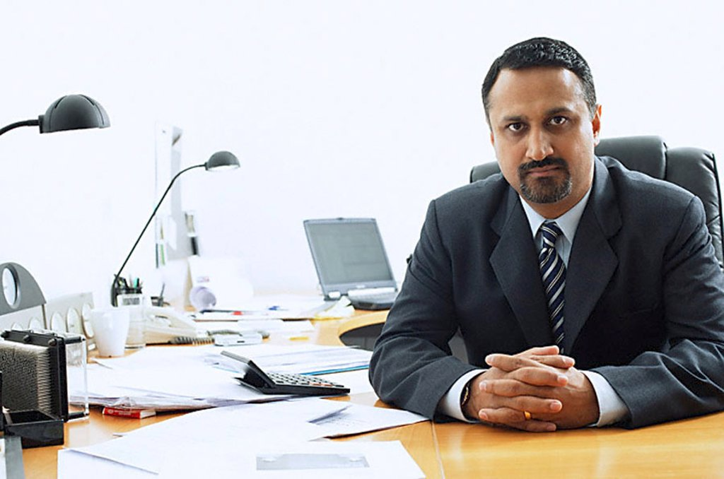 Businessman at desk, looking at camera : Stock Photo