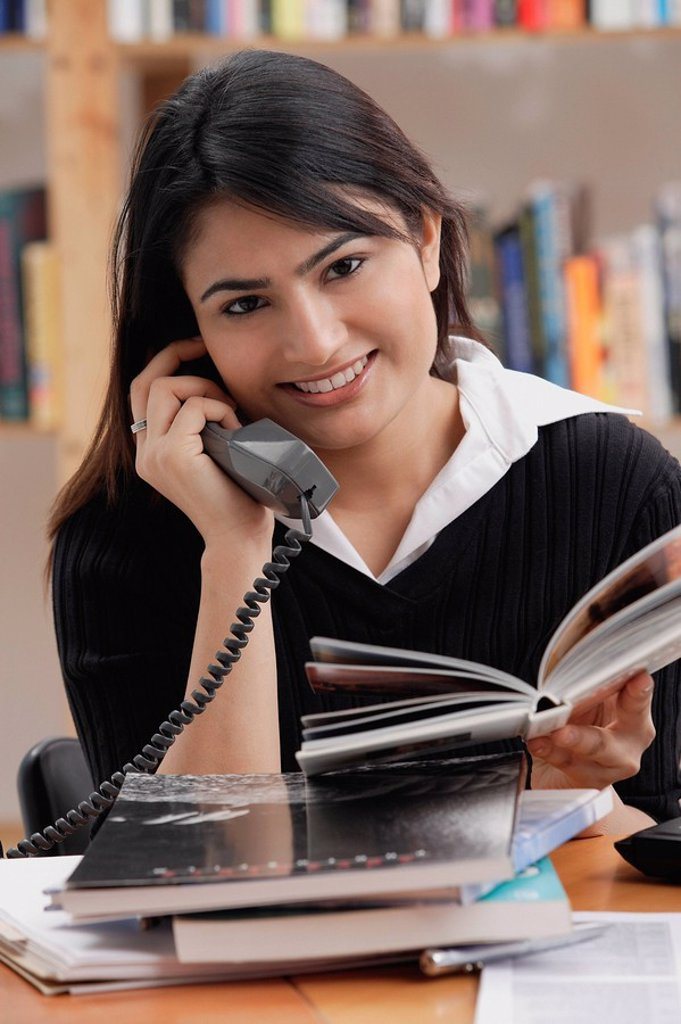 Stock Photo: 4078R-2724 Woman in library, using telephone, looking at camera