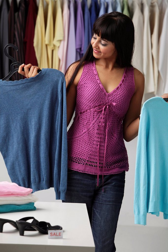 Stock Photo: 4078R-2957 woman looking at a sweater in shop