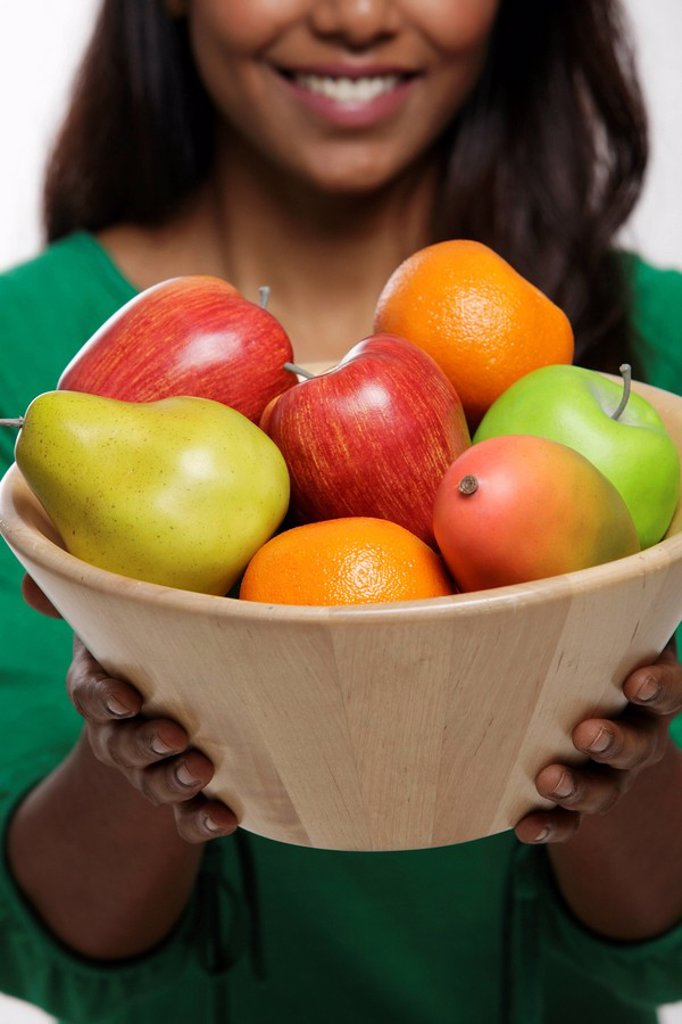 Young woman holding a bowl of fruit : Stock Photo