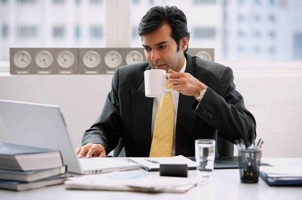 Businessman in office using laptop, drinking from cup : Stock Photo