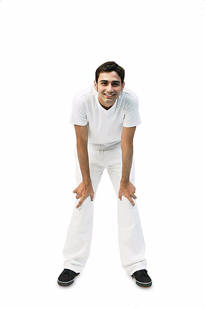 Young man bending, leaning on knee : Stock Photo