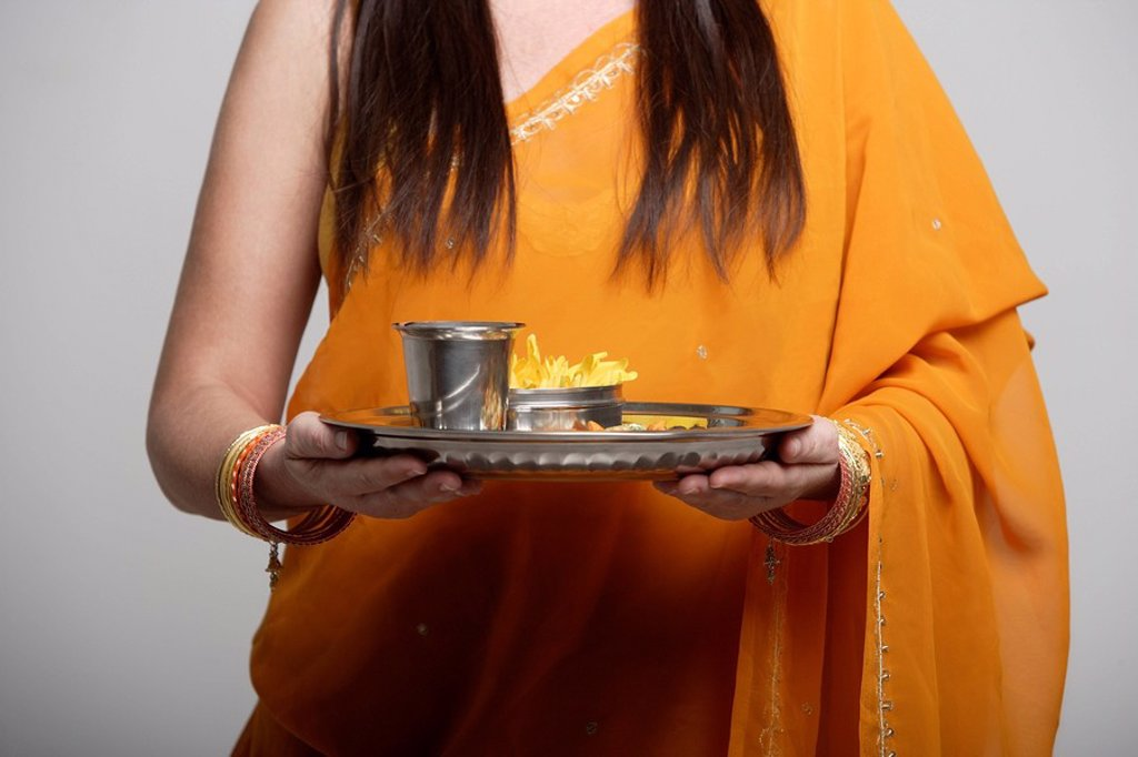 cropped shot of woman wearing a sari holding a tray with tea : Stock Photo