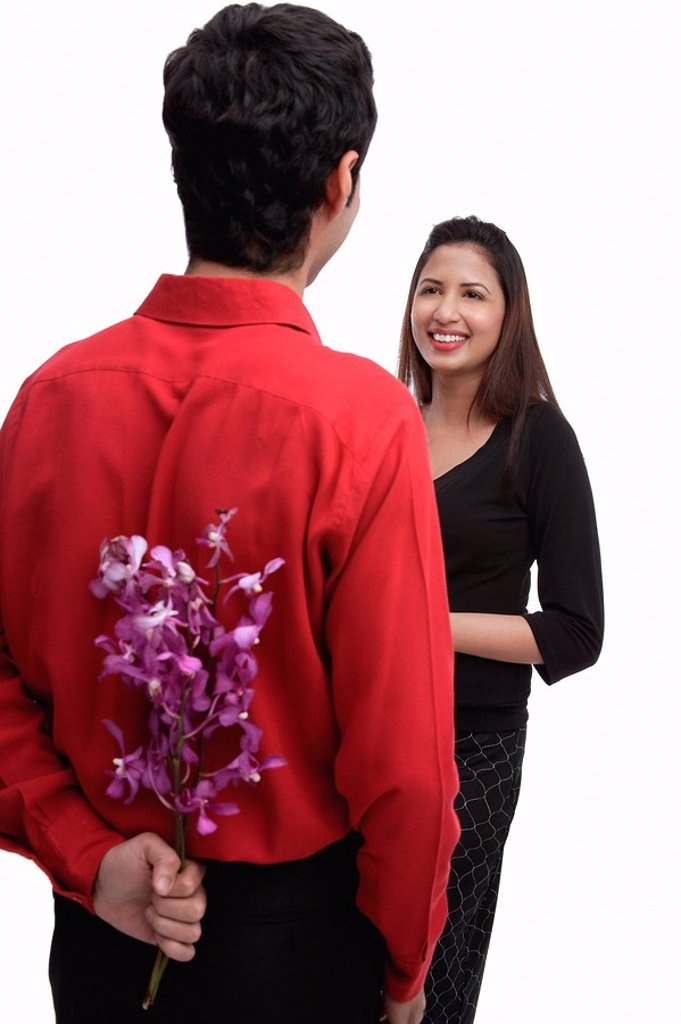 Man holding flowers behind his back, facing woman : Stock Photo