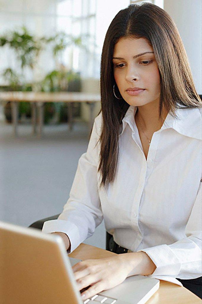 Female executive using laptop, portrait : Stock Photo