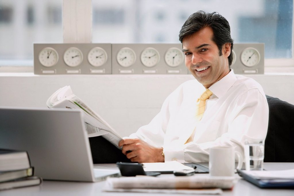 Businessman sitting in office, holding newspaper, smiling : Stock Photo