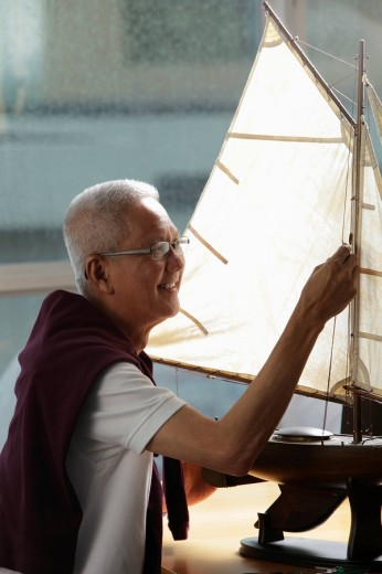 mature man working on model sail boat and smiling : Stock Photo