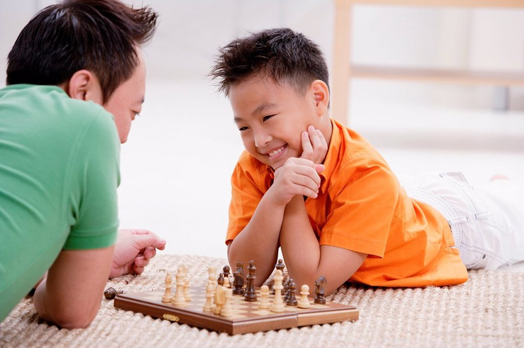 Father and son lying on floor, playing chess, smiling : Stock Photo