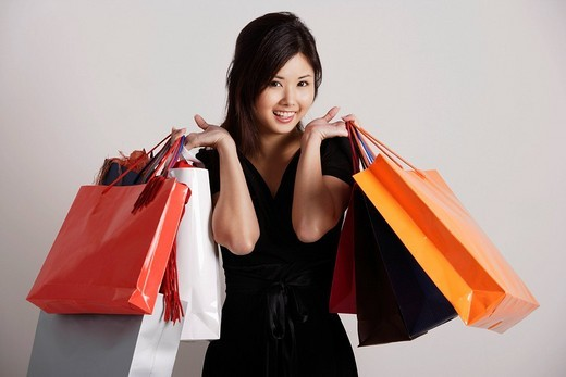 Stock Photo: 4079R-1377 Chinese woman holding shopping bags, smiling