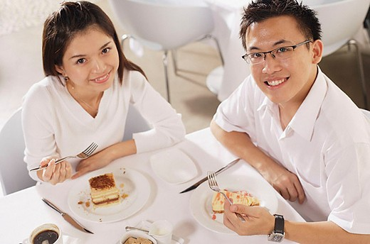 Couple eating dessert in restaurant, looking up at camera : Stock Photo