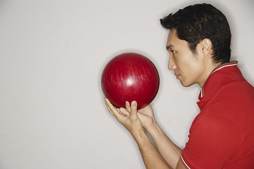 Man holding bowling ball in front of face, side view : Stock Photo