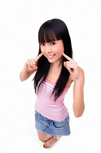 Young woman with fingers on cheek, smiling at camera : Stock Photo