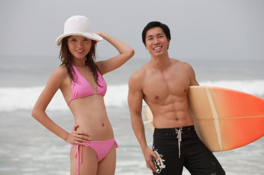 Stock Photo: 4079R-1855 Couple on beach, man carrying surfboard