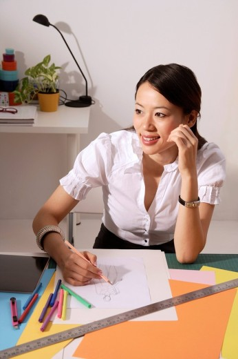 Stock Photo: 4079R-1986 Chinese fashion designer smiling, sketching at work desk