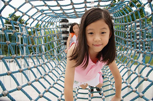 Girls at playground, going through net tunnel : Stock Photo