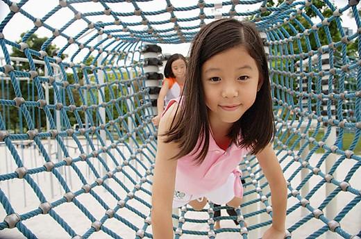 Stock Photo: 4079R-2201 Girls at playground, going through net tunnel