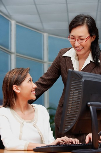 Female executive at computer, smiling at woman standing next to her : Stock Photo