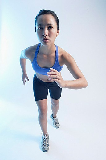 Woman in running position, facing forward : Stock Photo